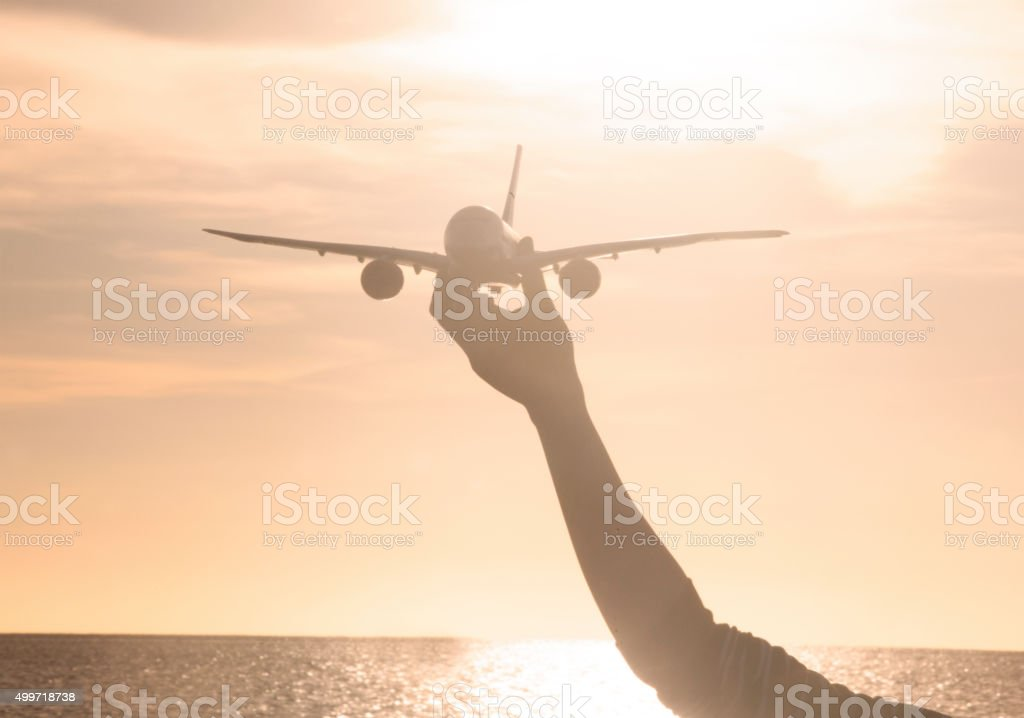 woman's hand holding toy airplane in sunset stock photo