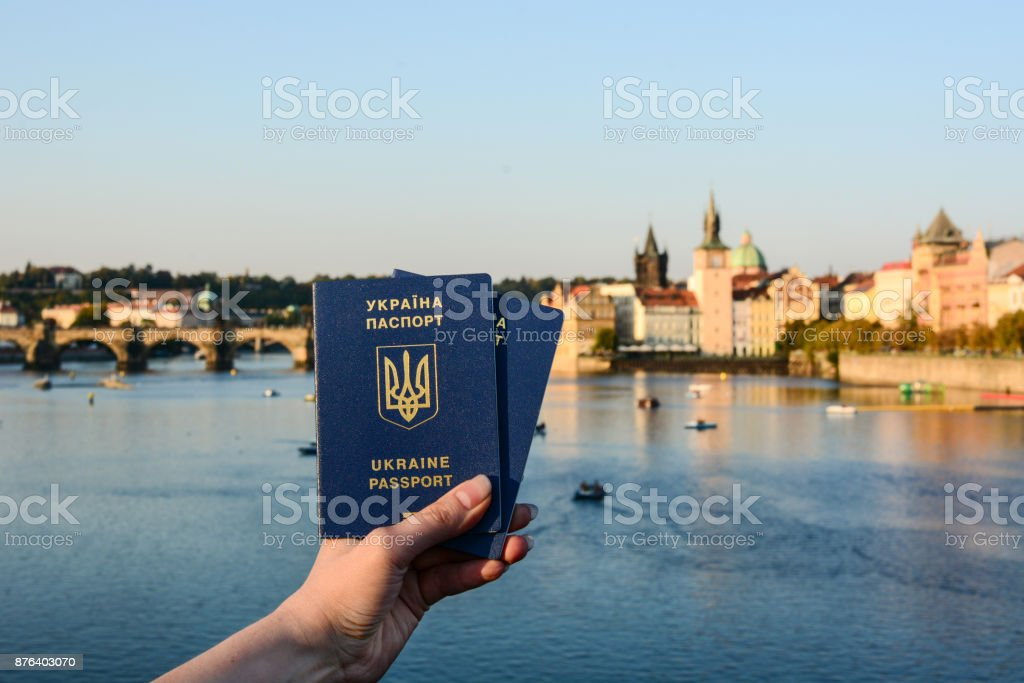 Woman's hand holding two Ukrainian passports in front of Prague old town cityscape stock photo