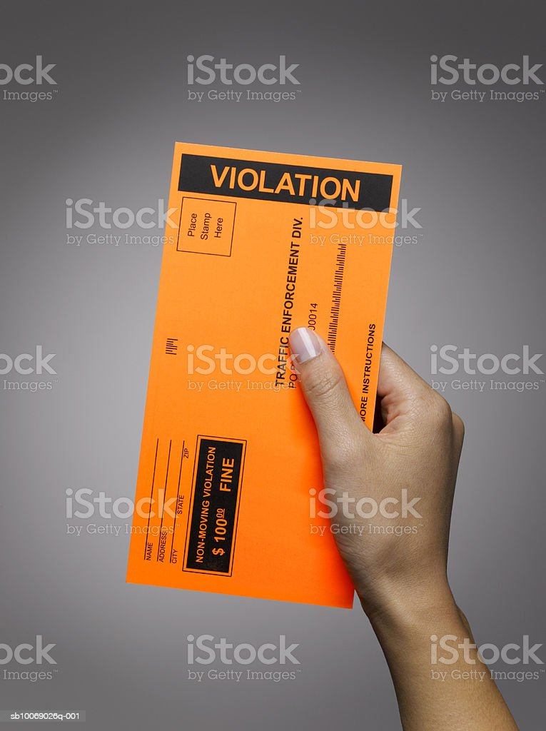Woman's hand holding violation ticket, studio shot royalty-free stock photo