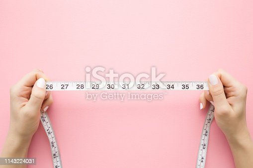 istock Woman's hand holding white measure tape on pastel pink background. Mock up for body slimming, weight loss or dressmaker's offer or other ideas. Empty place for text, logo or object. Top view. 1143224031