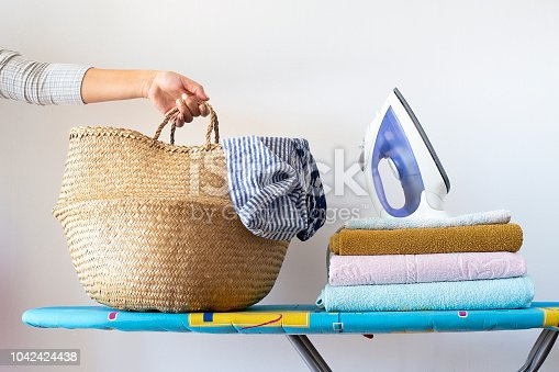 901620964 istock photo A woman's hand holds a basket with clean linen for ironing on the ironing board next to the iron and a pile of clean ironed towels. Homework Concept 1042424438
