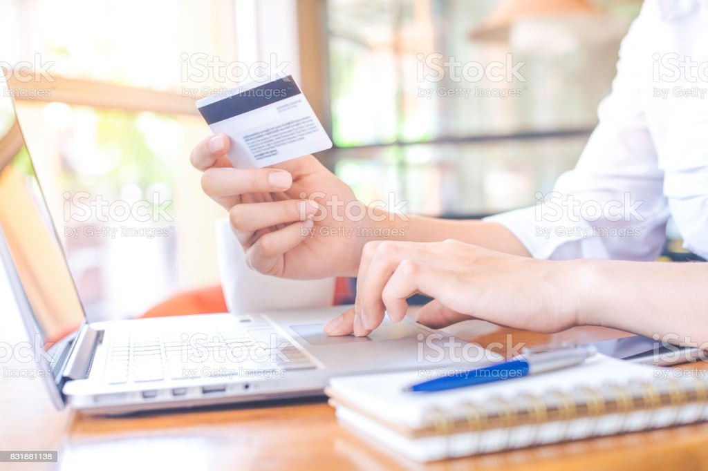 A woman's hand holds a credit card and uses  a  laptop computer to shop online. A woman's hand holds a credit card and uses  a  laptop computer to shop online. Adult Stock Photo
