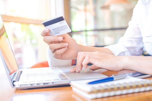 A Womans Hand Holds A Credit Card And Uses A Laptop Computer To Shop Online Stock Photo - Download Image Now