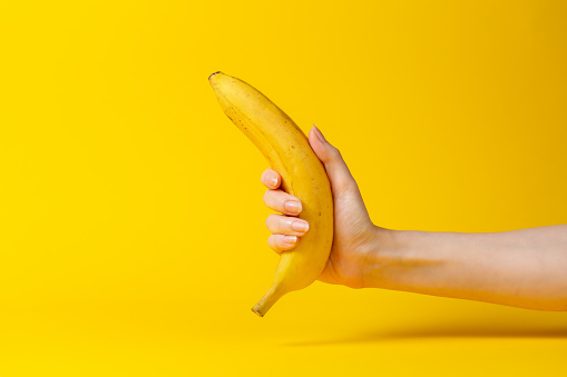 A woman's hand holds a ripe banana. Yellow background. Close up.