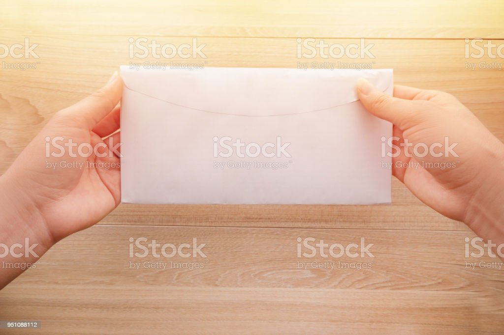 Woman\'s hand holds a white long paper envelope or letter envelopes on...