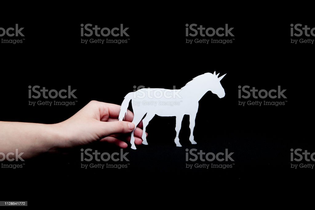 A woman\'s hand holds a white unicorn with a black background paper.