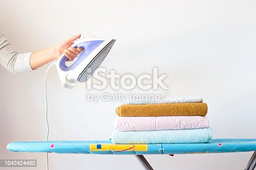 901620964 istock photo A woman's hand holds an iron over a pile of clean ironed towels on the ironing board. Homework Concept 1042424452
