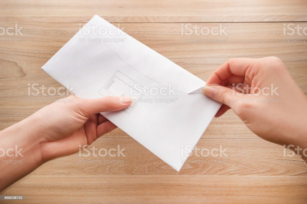 Woman\'s hand holds and opens a white paper envelope or letter...