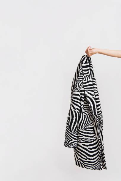 Cтоковое фото Woman's hand holds zebra patterned coat.