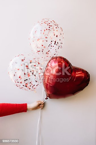 1016084100istockphoto Woman's hand in a red sweater holding a bunch of balloons with transparent glitter balloons and a heart-shaped balloon 936573530
