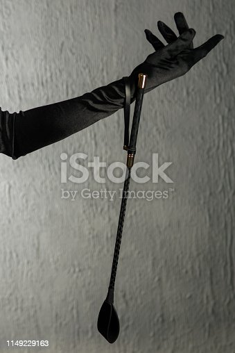 istock Woman's hand in a satin glove holding a stack. Bdsm outfit 1149229163