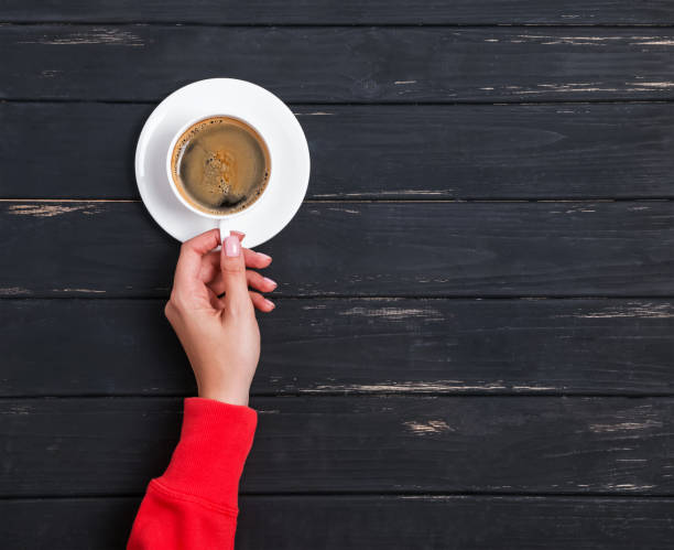 Woman's hand in red clothing holding a cup of coffee on the black wooden background stock photo