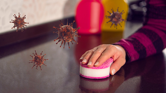 woman's hand is cleaning the countertop with a pink cleaning sponge. (covid-19)