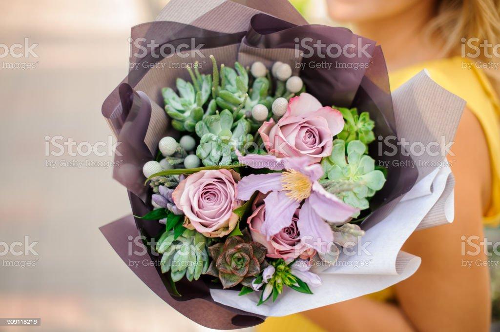 A womans hand is holding a bouquet of flowers стоковое фото