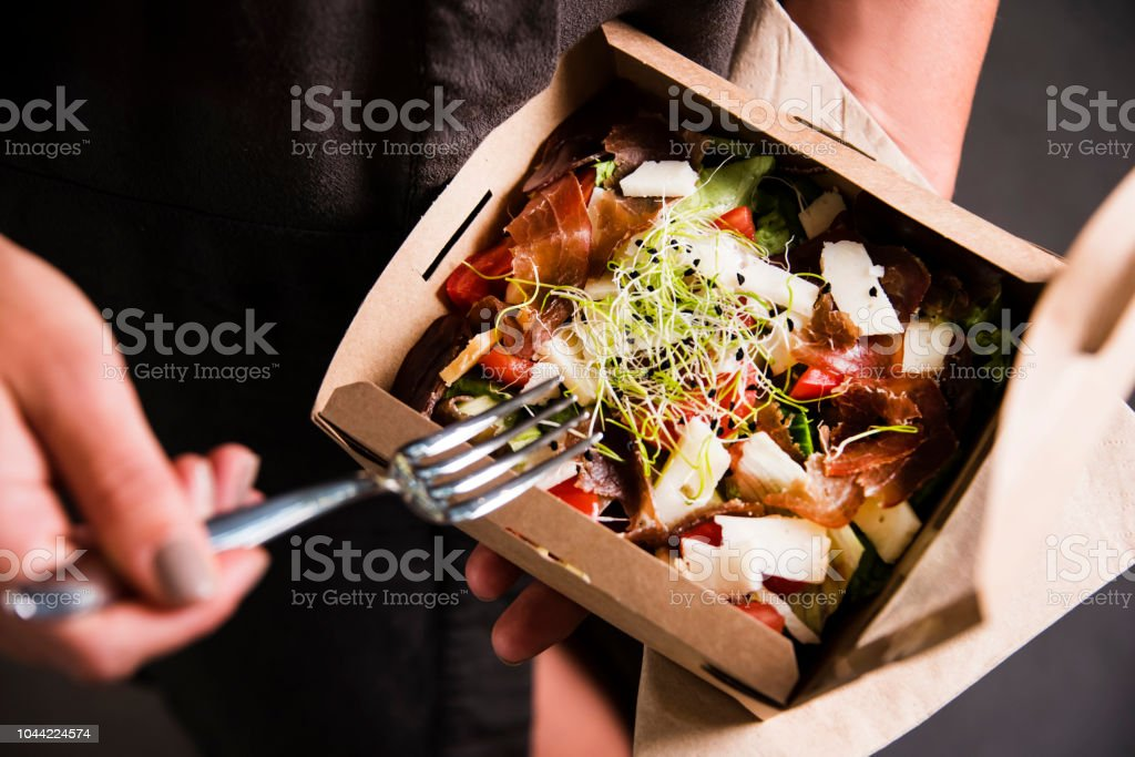Woman's hand is holding a take away fresh salad in a lunch box. stock photo