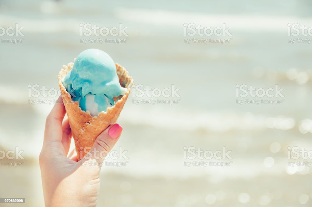 Woman's hand is holding ice cream on sea background. Summer. Vacation. stock photo