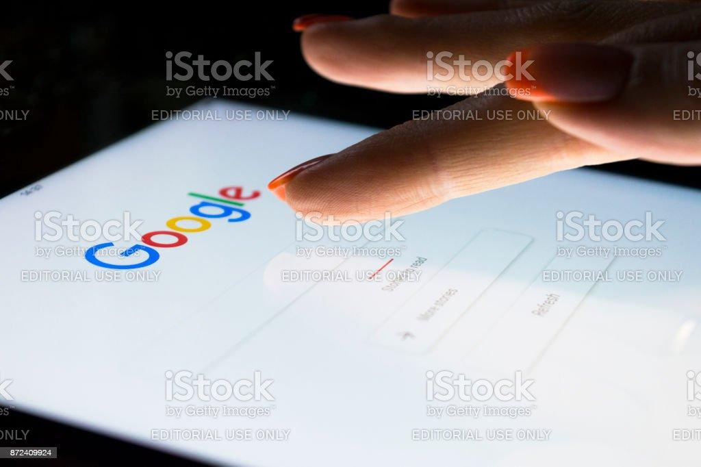 Die Hand einer Frau berührt Bildschirm auf dem Tablet Computer iPad Pro in der Nacht für die Suche auf Google Search Engine. Google ist die beliebteste Internet-Suchmaschine der Welt. – Foto
