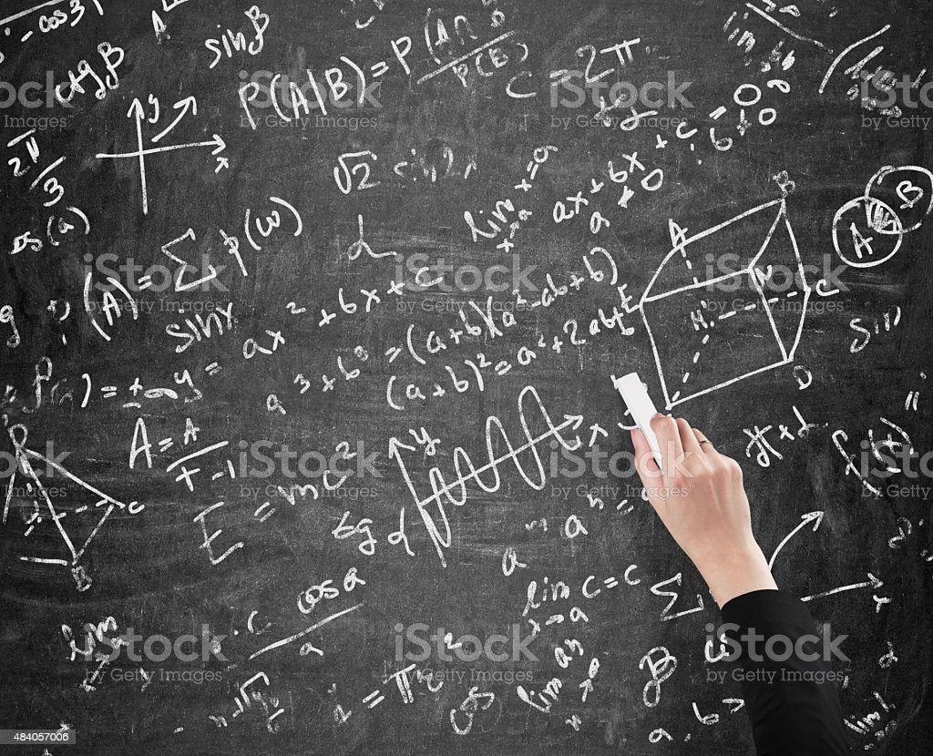 woman's hand is writing math calculations stock photo