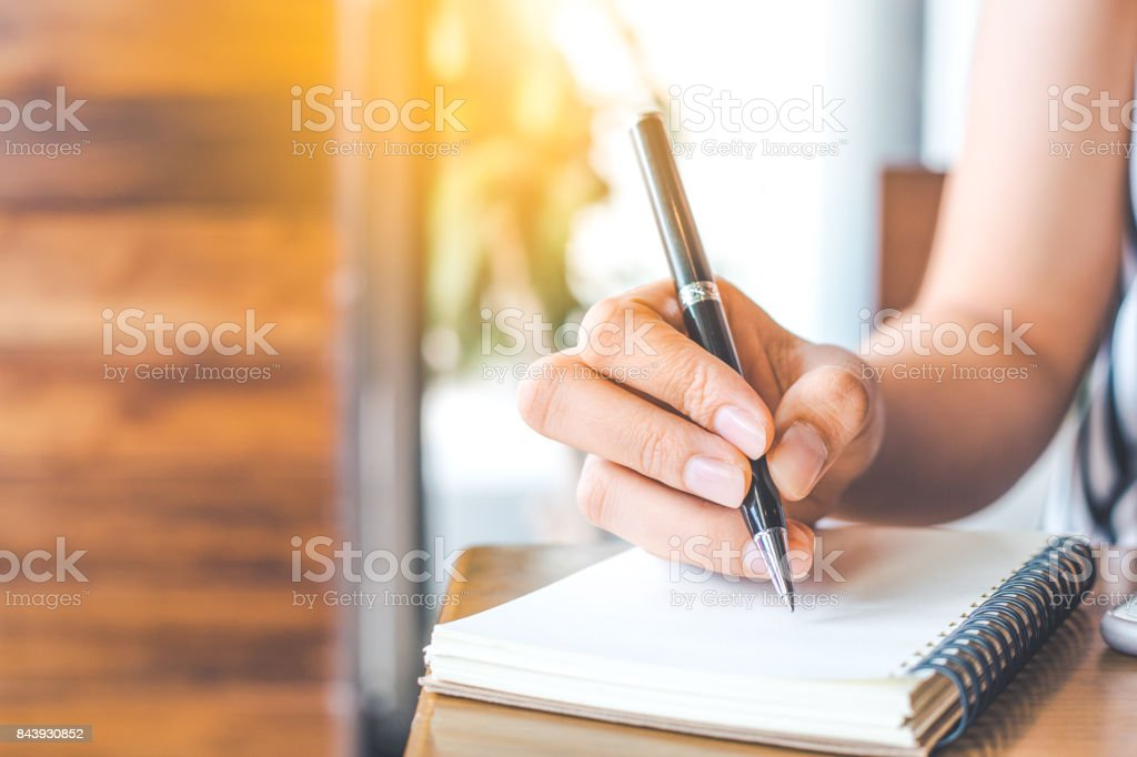 woman's hand is writing on a blank notepad with a pen on a wooden desk. stock photo