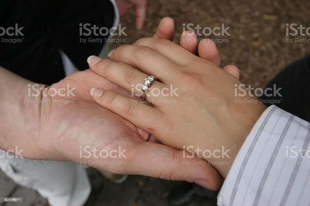 Woman's hand on top of man's royalty-free stock photo