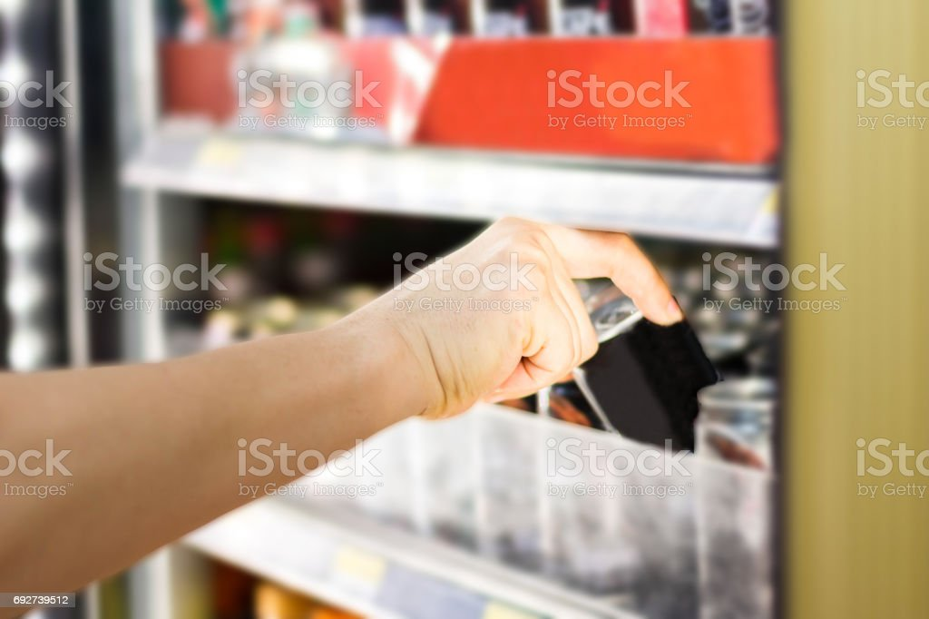 woman's hand open convenience store refrigerator shelves and pick product stock photo