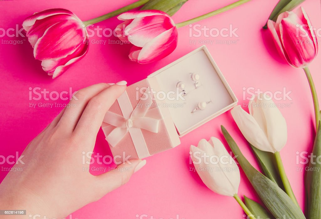 Woman's hand opening a box with jewellery surrounded with tulips stock photo