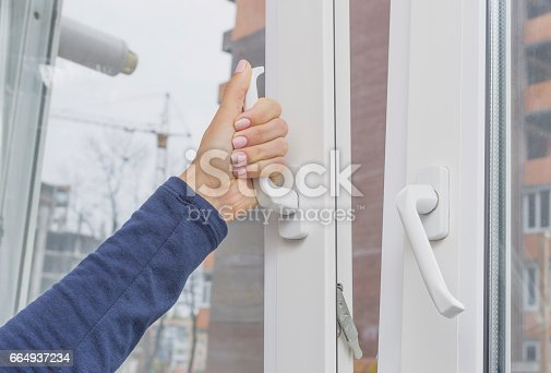 istock Woman's hand opening a window 664937234