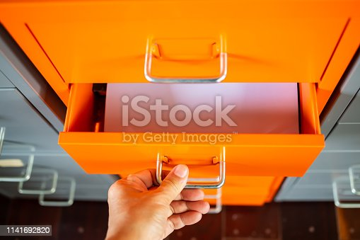 535191355istockphoto Woman's hand opening drawer of orange metal colour  filing cabinet, White papers for write letter, Administration and storage, Close up shot, Selective focus, Stationery, Business concept 1141692820