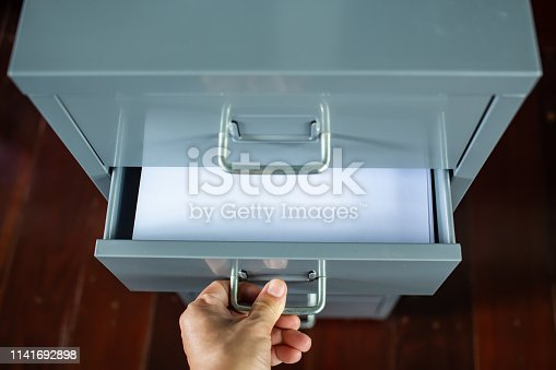 535191355istockphoto Woman's hand opening drawer of silver grey metal colour filing cabinet, White papers for write letter, Administration and storage, Close up shot, Selective focus, Stationery, Business concept 1141692898