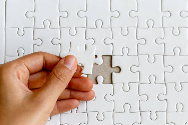 Woman's hand placing put the last white jigsaw puzzle piece to complete the mission, business success concept Woman's hand placing put the last white jigsaw puzzle piece to complete the mission, business success concept jigsaw piece stock pictures, royalty-free photos & images