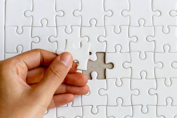 zarte frauenhand platzierung legte das letzte weiße jigsaw puzzlestück zur vervollständigung der mission, die geschäftsidee erfolg - puzzleteile stock-fotos und bilder