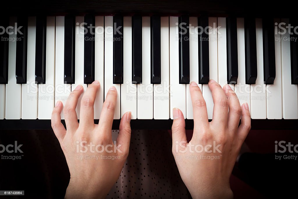 Woman's hand playing piano. stock photo
