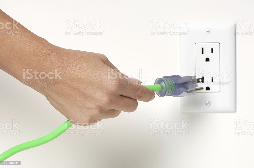 Woman's Hand Plugging Electrical Cord into Socket royalty-free stock photo