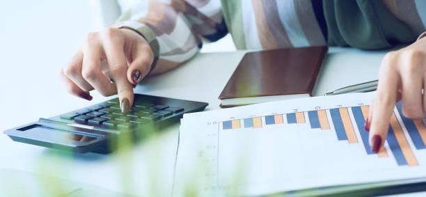 Die Hand einer Frau zeigt auf dem übersichtlichen Berichtsdiagramm und berechnet die Finanzsumme in der Nähe des Büros. – Foto