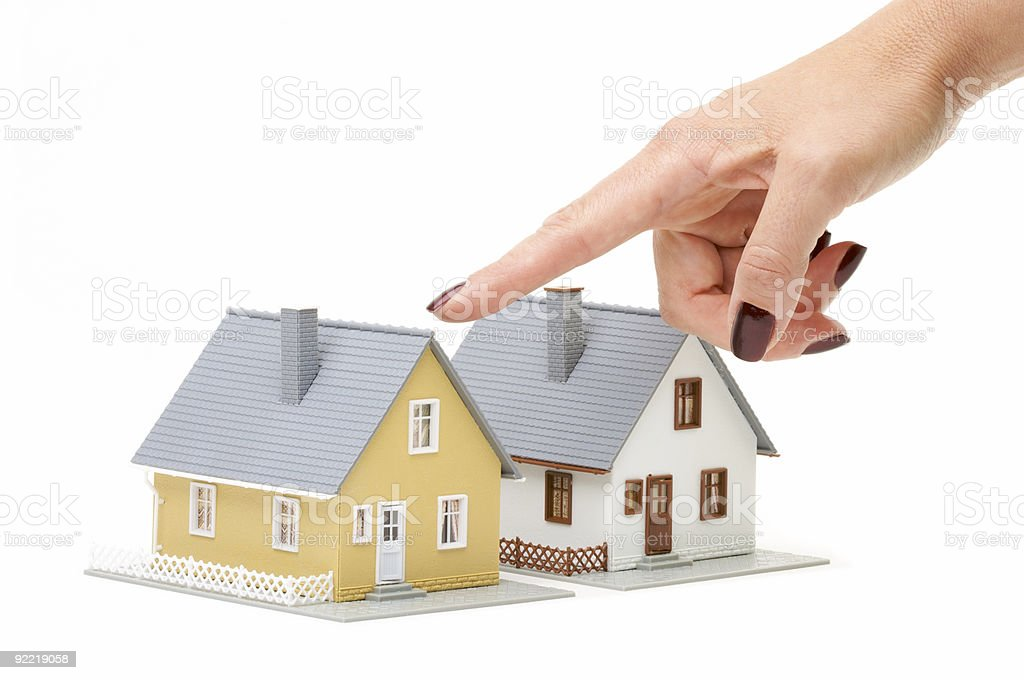 Womans Hand Pointing To Small Model Homes on White royalty-free stock photo