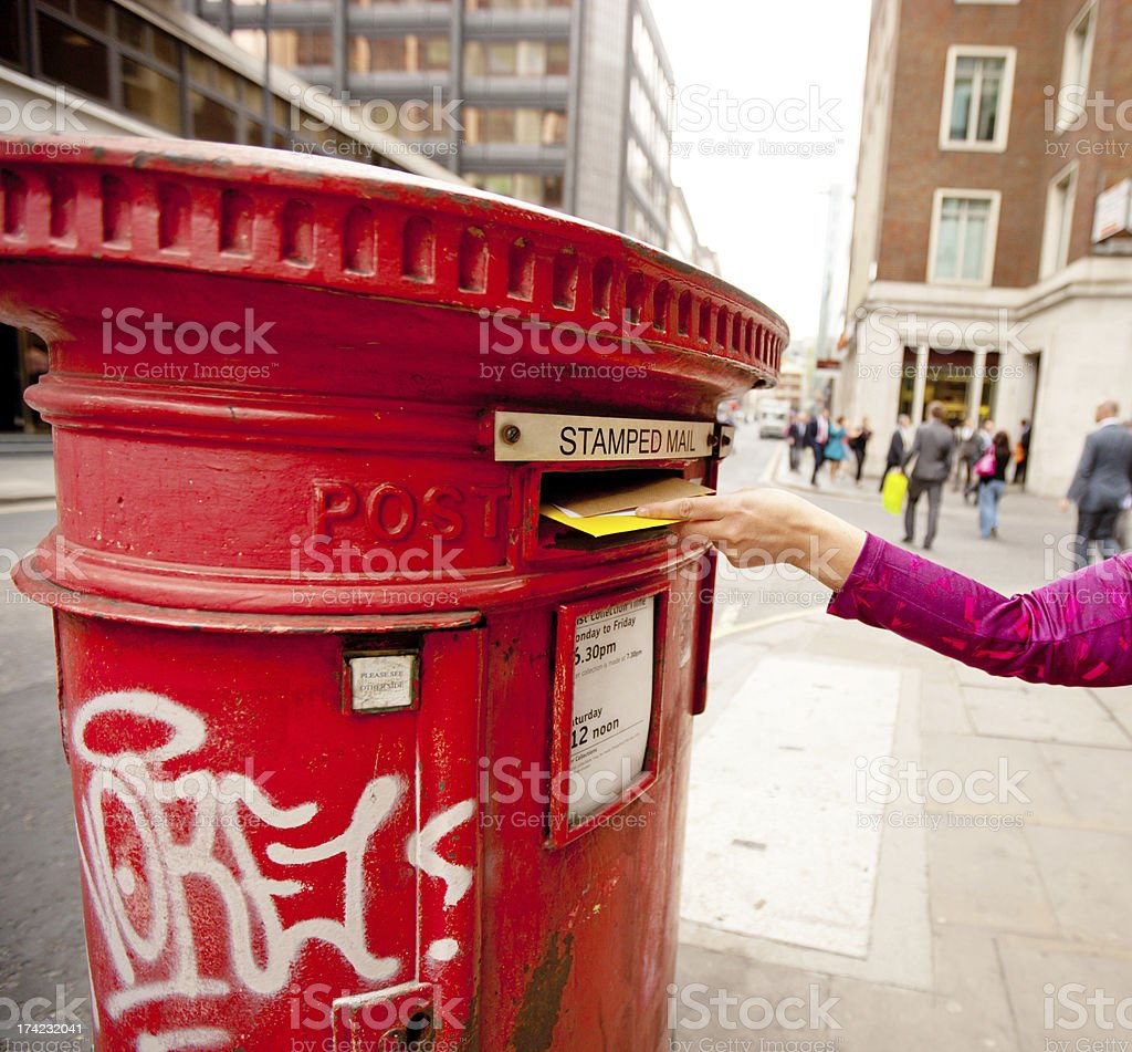 Woman's hand posting letters in traditional British mailbox royalty-free stock photo