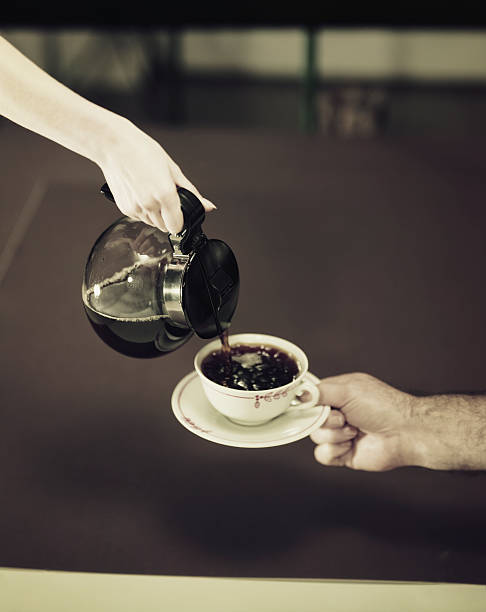 Woman's hand pouring coffee into cup held by man's hand  early 20th century stock pictures, royalty-free photos & images