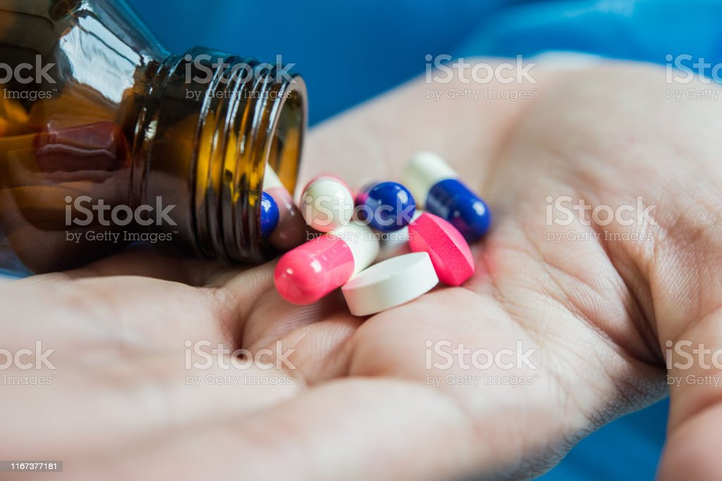 Woman\'s hand pours the medicine pills out of the bottle