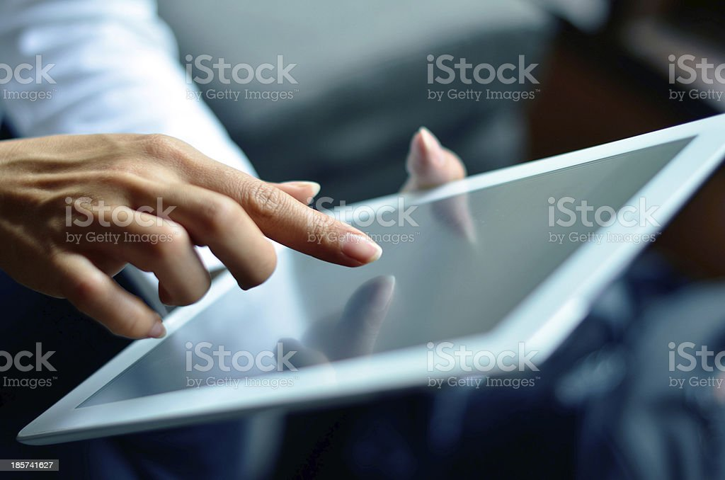 Woman's hand presses on digital tablet stock photo