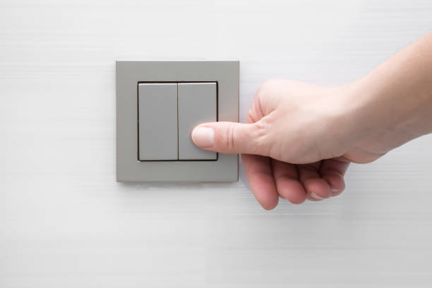 main pressant interrupteur femme au mur. - commutateur photos et images de collection