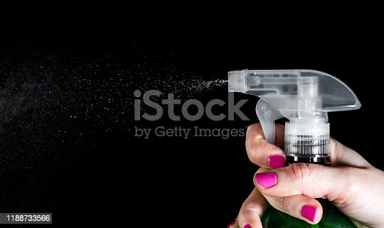Woman's hand pressing on sprayer. Isolated on black.
