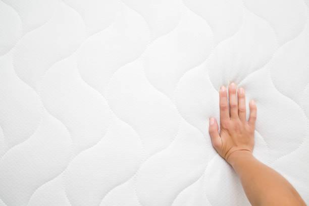 白いマットレスの上を押すと女性の手。硬さと柔らかさをチェックします。最高の型と品質の選択。ビューのポイントを撮影しました。領域をコピーします。テキストまたはロゴの空の場所� - 布団 ストックフォトと画像