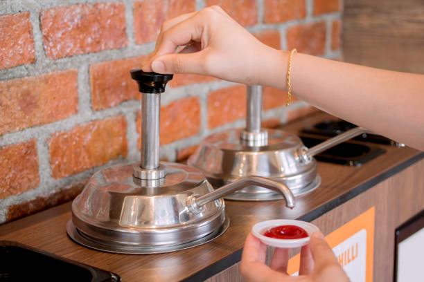Woman's hand pumping the ketchup stock photo