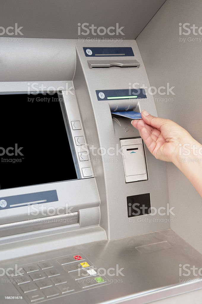 Woman's hand puts bank card into ATM royalty-free stock photo