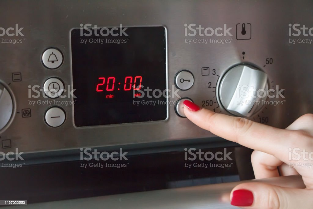 A womans hand puts on the oven a time of 20 minutes and a temperature...