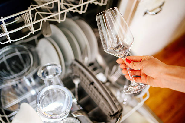 Woman's hand putting wine glass in the washer Close up image of a young woman's hand taking a clean wine glass out of the dishwasher machine in her apartment in Paris, France. House work, domestic work concepts in a modern, French kitchen. dishwasher stock pictures, royalty-free photos & images