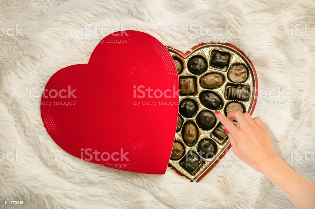 A woman's hand reaching for a chocolate candy stock photo