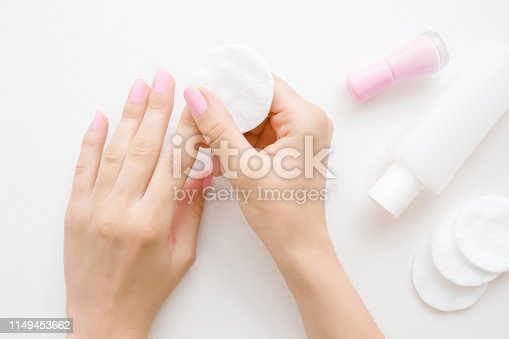 1147741037 istock photo Woman's hand removing pink nail polish with white cotton pad on table. Point of view shot. Closeup. Top view. 1149453662