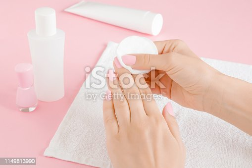 istock Woman's hand removing pink nail polish with white cotton pad on towel. Closeup. 1149813990