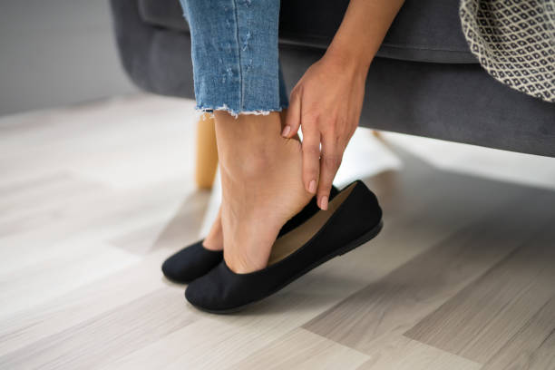 Woman's Hand Removing Uncomfortable Ballerinas Close-up Of Woman's Hand Sitting On Sofa Removing  Uncomfortable Ballerinas blister stock pictures, royalty-free photos & images